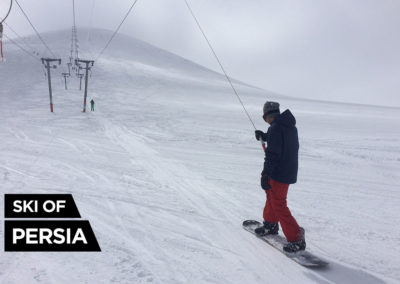 A snowboarder going up the Sahand's slope with the ski-lift